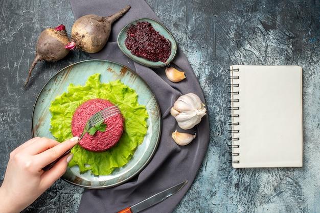 Bovenaanzicht bietensalade op plaat knoflookbieten geraspte biet in kleine komvork in vrouwelijke hand paarse sjaal notebook op grijze tafel