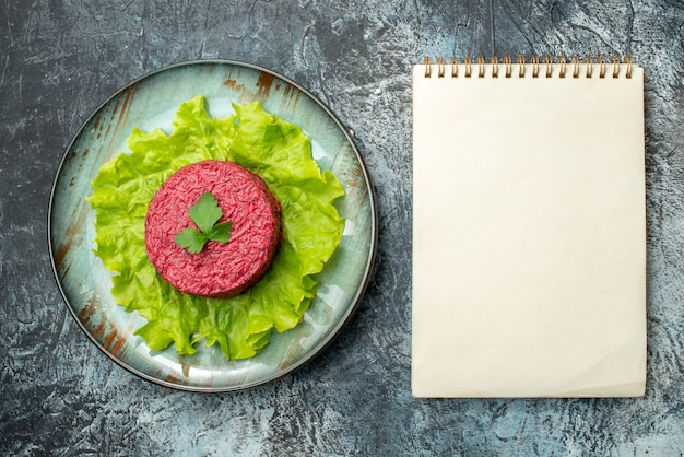 Bovenaanzicht bietensalade op schotel notitieblok op grijze tafel