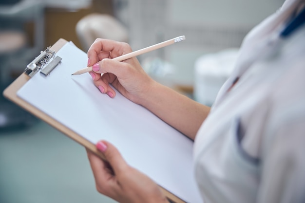 Bovenaanzicht bijgesneden hoofd close-up van vrouw die klembord vasthoudt en informatie schrijft tijdens bezoek aan tandheelkundige kliniek
