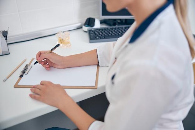 Bovenaanzicht bijgesneden hoofd van vrouwelijke tandarts zittend aan tafel met computer en recept maken