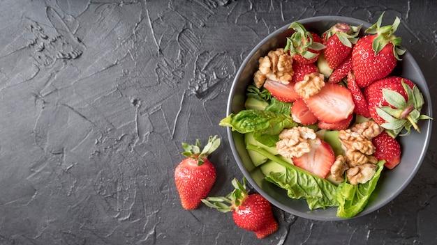 Bovenaanzicht biologische salade met walnoten en aardbeien