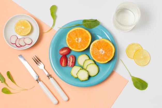 Bovenaanzicht biologische sinaasappelen en groenten op een bord