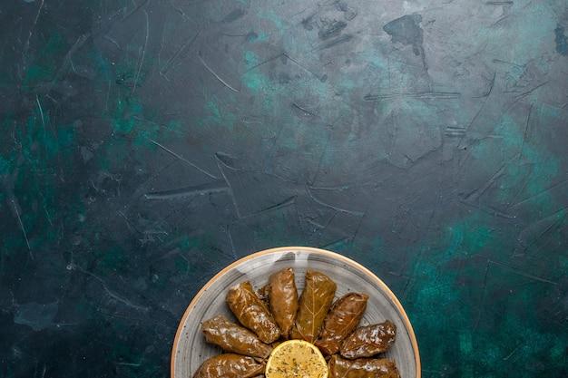 Bovenaanzicht blad dolma heerlijke oosterse vleesmaaltijd binnen gerold groene bladeren op het donkerblauwe bureau vleesmaaltijd eten diner schotel groente gezondheid calorieën