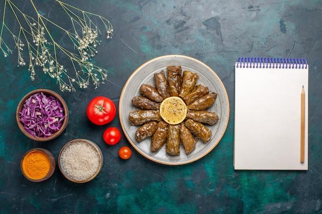 Bovenaanzicht blad dolma heerlijke oosterse vleesmaaltijd gerold in groene bladeren met tomaten en kruiden op het blauwe bureau vlees eten diner schotel groente gezondheid