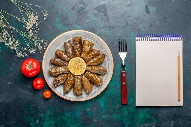 Bovenaanzicht blad dolma heerlijke oosterse vleesmaaltijd gerold in groene bladeren met verse tomaten op het blauwe bureau vlees eten diner schotel plantaardige gezondheid