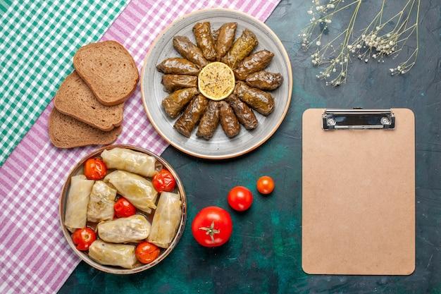Bovenaanzicht blad dolma oosterse vleesmaaltijd gerold in groene bladeren met kool dolma en brood op donkerblauw bureau vlees diner schotel oost maaltijd calorie