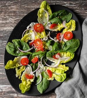 Bovenaanzicht blad vegetarische salade en tomaten