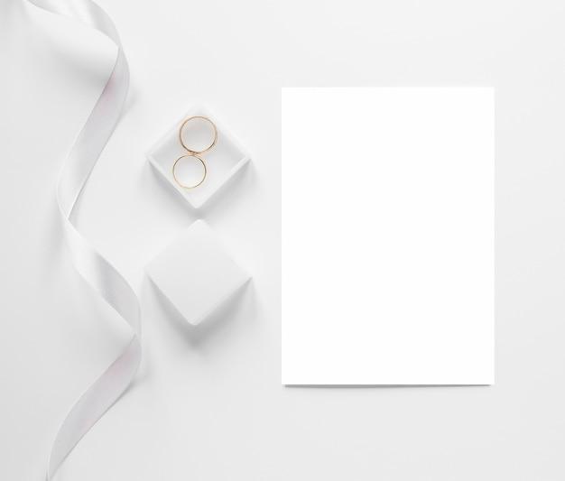 Bovenaanzicht blanco vel papier naast verlovingsringen