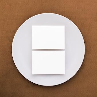 Bovenaanzicht blanco visitekaartjes op een bord