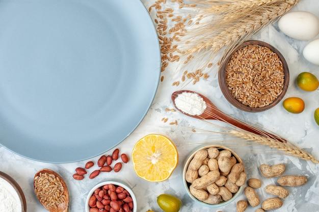 Bovenaanzicht blauw bord met meelgelei-eieren en verschillende noten op een deeg met witte suikerkleur, fruitfoto, taartnoot, zoete cake