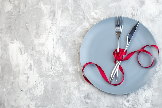 Bovenaanzicht blauw bord met vork en mes op lichte ondergrond keuken dames horizontaal voedsel kleur maaltijd glas familie vrouwelijkheid