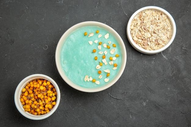 Bovenaanzicht blauw ijsdessert met rauwe muesli op donkere roomijskleur van de tafel