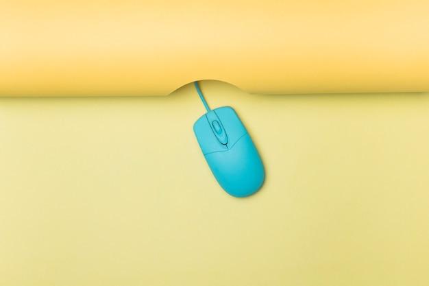 Bovenaanzicht blauwe computermuis met gele achtergrond