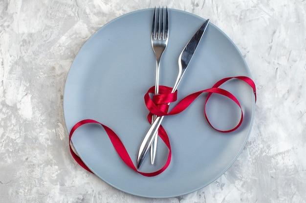 Bovenaanzicht blauwe plaat met vork en mes op lichte ondergrond keuken dames horizontaal eten maaltijd glas familie vrouwelijkheid