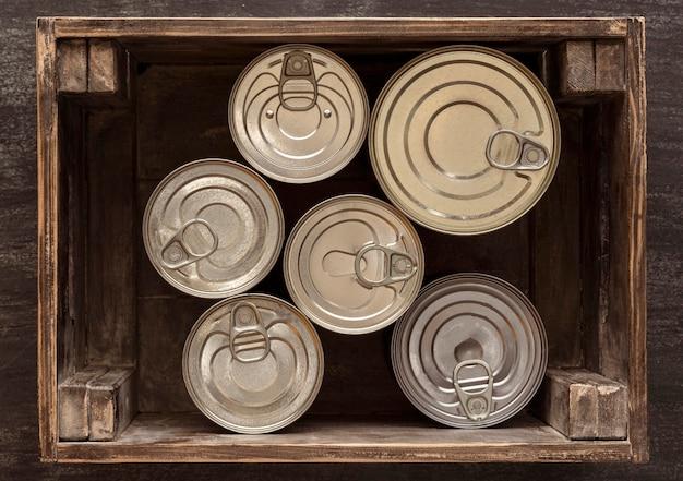 Bovenaanzicht blikjes in houten kist