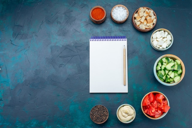 Bovenaanzicht blocnote en groenten met kruiden op de donkerblauwe achtergrondkleur van de maaltijd van de groente-snackmaaltijd