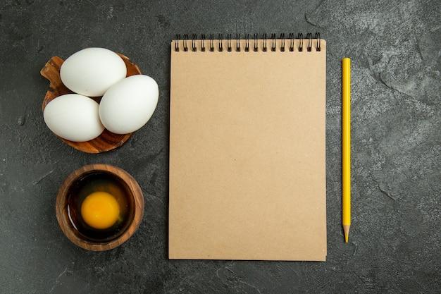 Bovenaanzicht blocnote en potlood met eieren op grijze ruimte