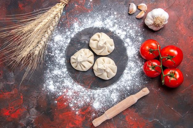 Bovenaanzicht bloem meel drie khinkali tomaten knoflook deegroller