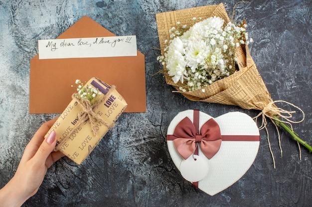 Bovenaanzicht bloemboeket hartvormige doos cadeau in vrouwelijke hand liefdesbrief op donkere achtergrond
