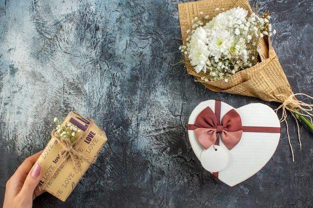 Bovenaanzicht bloemboeket hartvormige doos cadeau in vrouwelijke hand op donkere achtergrond kopie plaats