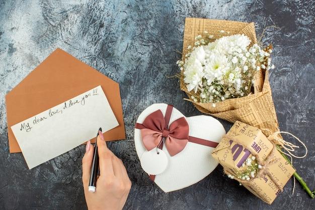Bovenaanzicht bloemboeket hartvormige doos geschenk liefdesbrief pen in vrouwelijke hand op donkere achtergrond