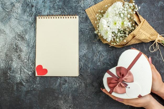 Bovenaanzicht bloemboeket hartvormige doos in vrouwelijke handen notebook op donkere achtergrond