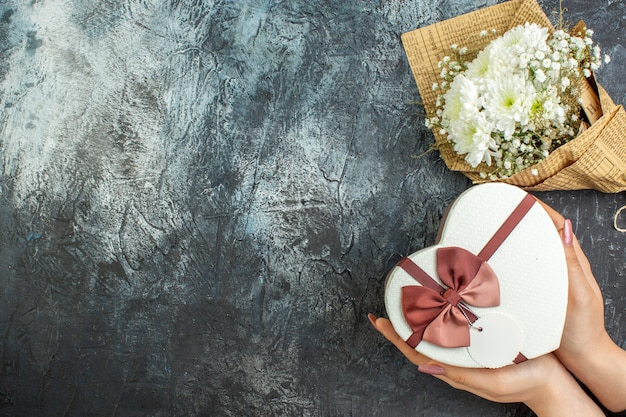 Bovenaanzicht bloemboeket hartvormige doos in vrouwelijke handen op donkere achtergrond kopie plaats