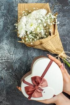 Bovenaanzicht bloemboeket hartvormige doos in vrouwelijke handen op donkere achtergrond