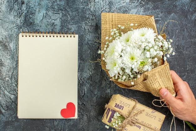 Bovenaanzicht bloemboeket in vrouwelijke hand cadeau notebook op donkere achtergrond