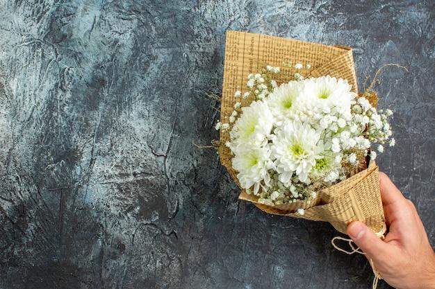 Bovenaanzicht bloemboeket in vrouwelijke hand op donkere achtergrond kopie plaats
