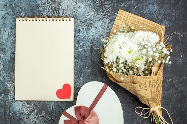 Bovenaanzicht bloemboeket notebook hartvormige doos op donkere achtergrond