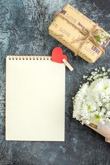 Bovenaanzicht bloemboeket verpakt cadeau notitieboekje met kleine hartsticker op donkere achtergrond