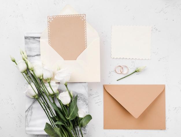 Bovenaanzicht bloemen met bruiloft uitnodigingskaarten