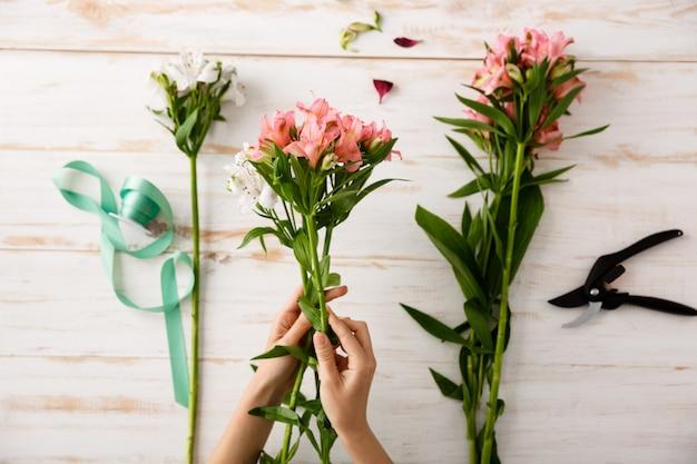 Bovenaanzicht bloemist handen maken bloemboeket