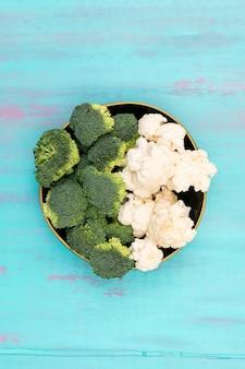 Bovenaanzicht bloemkool en broccoli in keramische kom op blauwe ondergrond