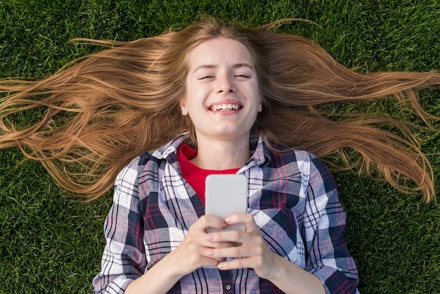 Bovenaanzicht blonde meisje houdt van haar telefoon