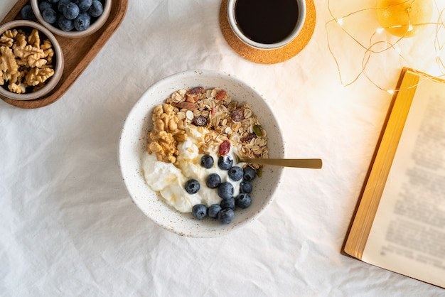 Bovenaanzicht boek en gezonde levensstijl ontbijt met muesli muesli en yoghurt
