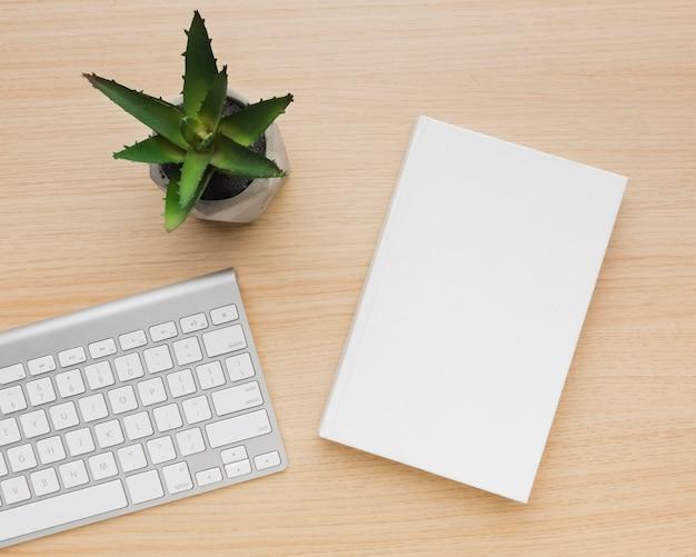 Bovenaanzicht boek op tafel met plant naast