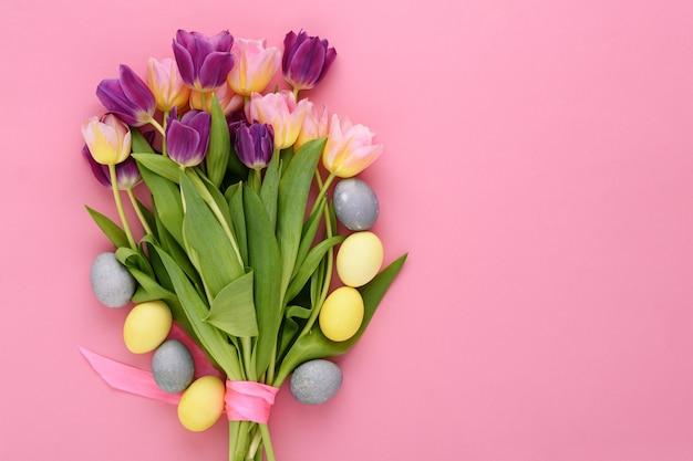 Bovenaanzicht boeket van roze en lila tulpen en pasen pastel gele, blauwe eieren op roze achtergrond met kopie ruimte, pasen boeket concept