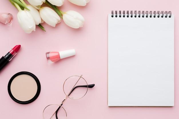 Bovenaanzicht boeket van tulpenbloemen en make-up met kladblok
