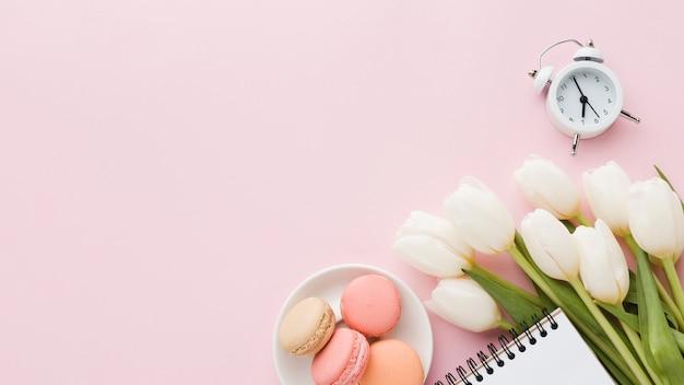 Bovenaanzicht boeket van tulpenbloemen met snoep en klok