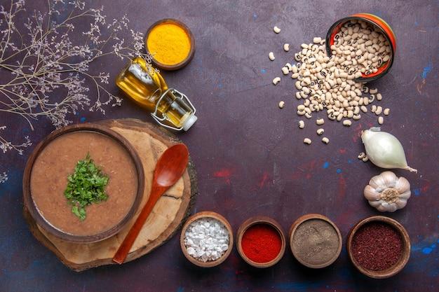 Bovenaanzicht bonensoep heerlijke gekookte soep met kruiden op het donkere oppervlak soepboon kleur pittige maaltijd