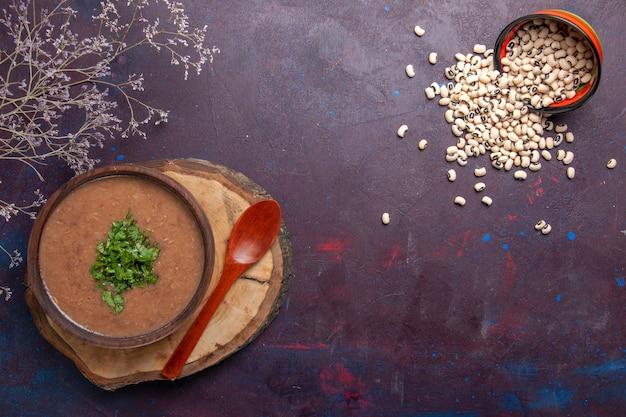 Bovenaanzicht bonensoep heerlijke gekookte soep op het donkere oppervlak soepboon kleur pittige maaltijd