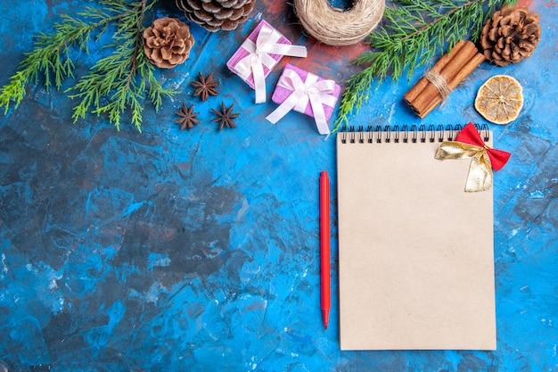 Bovenaanzicht boog op een notebook pijnboomtakken kaneelstokjes anijs gedroogde citroen plakjes op blauwe oppervlakte vrije ruimte