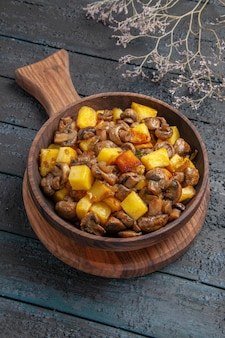 Bovenaanzicht bord aan boord bruin bord aardappelen met champignons op de snijplank op de donkere tafel naast de boomtakken