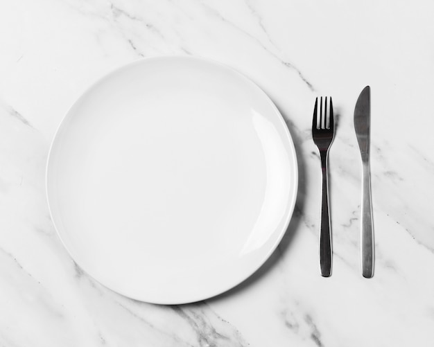 Bovenaanzicht bord en bestek op marmeren tafel