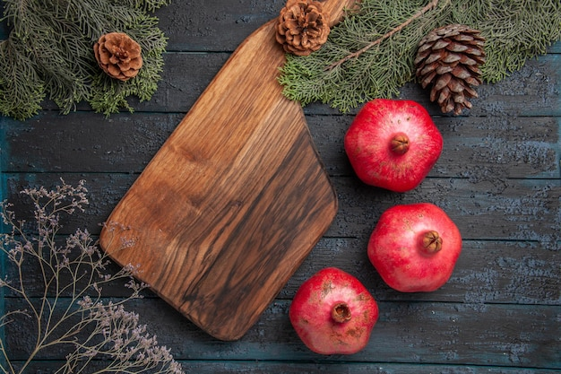Bovenaanzicht bord en granaatappels rijpe rode granaatappels naast keukenbord en spuce-takken met kegels