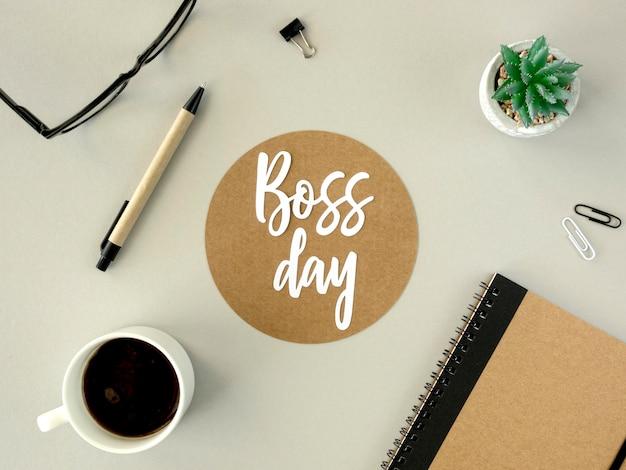 Bovenaanzicht bord met baas dag op bureau