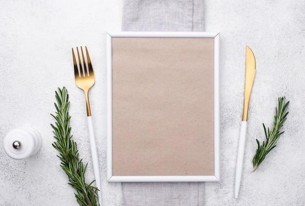 Bovenaanzicht bord met bestek en frame