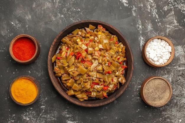 Bovenaanzicht bord met bonen bruin bord met sperziebonen en tomaten tussen kommen met kruiden op de donkere tafel